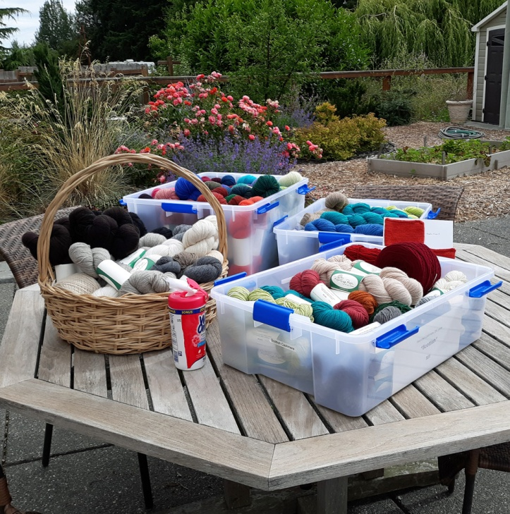 Containers of recycled cashmere outdoors on picnic table.